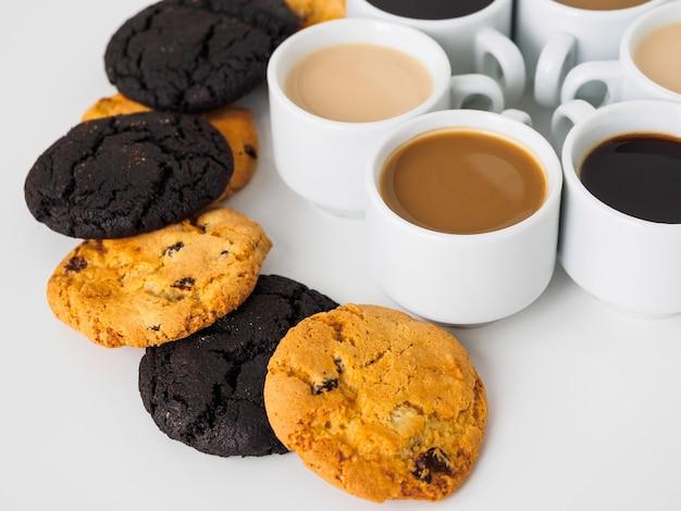 Unterschiedlicher kaffee in weißen bechern und keksen auf einem weißen tisch