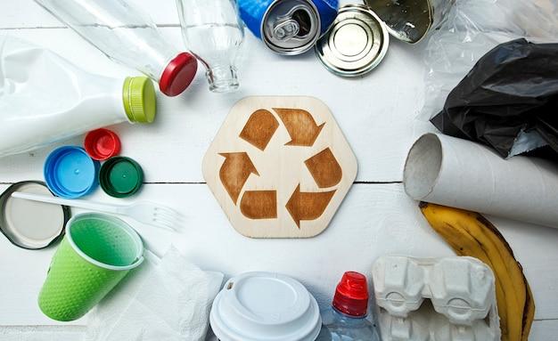 Unterschiedlicher müll auf dem tisch und recycling-symbol zwischen ihnen