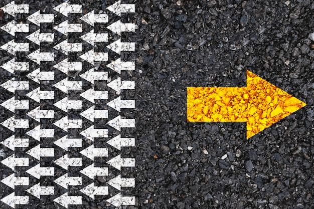 Unterschiedliches denken und konzept von geschäfts- und technologieunterbrechungen. gelber pfeil entgegengesetzter richtung mit weißem pfeil auf straßenasphalt.