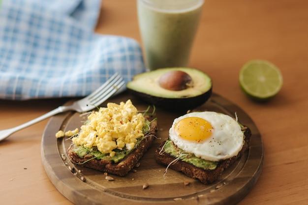 Unterschiedliches gekochtes ei auf avocadosandwich mit vollkornbrot auf holzbrett. smoothie mit spinat