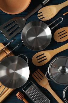 Unterschiedliches küchengerät auf blauem hölzernem hintergrund.