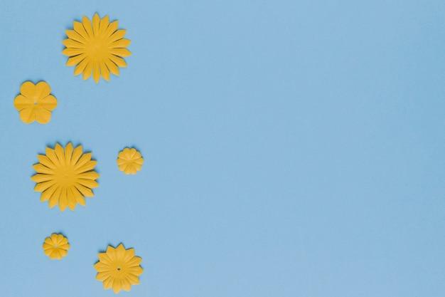 Unterschiedliches muster des gelben blumenausschnitts auf blauem hintergrund