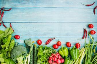 Unterschiedliches rohes Gemüse auf blauem Holztisch