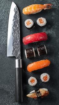 Unterschiedliches sushi mit japanischem messer. flach liegen.