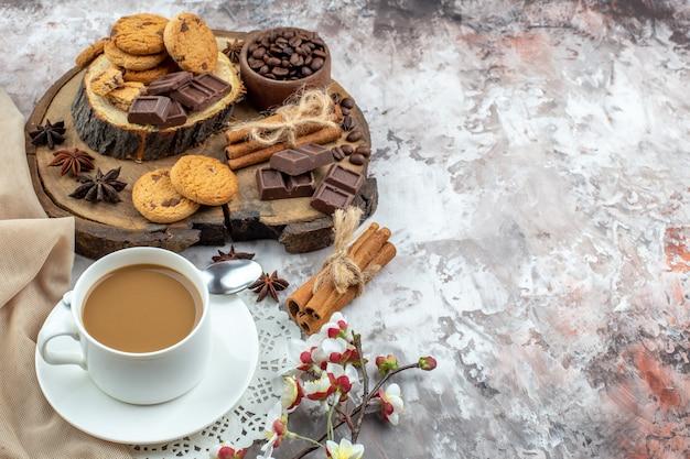 Untersicht tasse kaffeeschale mit gerösteten kaffeebohnen und kakao schokolade zimtstangen kekse auf holzbrett auf tisch freiraum