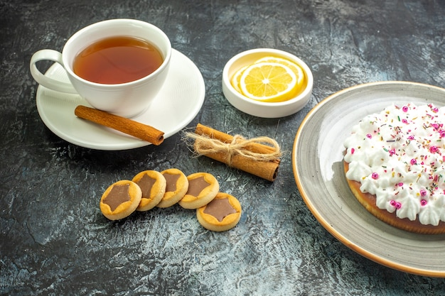 Untersicht tasse tee aromatisiert mit zimt zitronenscheiben in kleinen untertassen kekse zimtstangen auf dunklem tisch