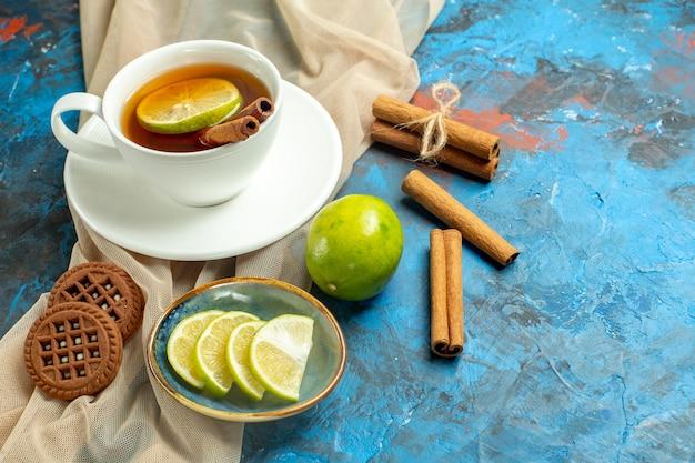 Untersicht tasse tee mit zitrone und zimt beige schalkekse zitrone auf blauroter oberfläche