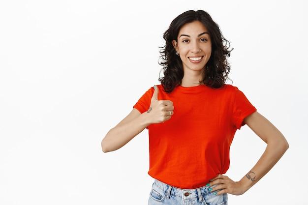 Unterstützende freundin zeigt daumen hoch, lächelt und sieht stolz aus, zufrieden mit guten ergebnissen, lob und komplimente für gute arbeit, genehmigen, mögen und stimmen zu weiß