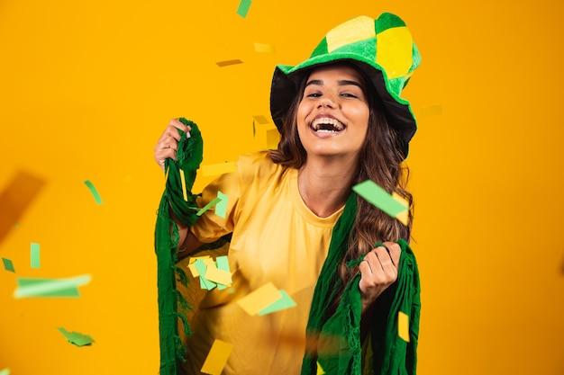 Unterstützer der jungen frau aus brasilien mit flagge und gekleidet für das spiel.