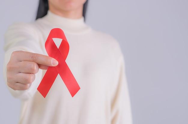 Unterstützt rotes band in der hand der frau für welthilfetag und nationales hiv / aids- und alternbewusstseinsmonatskonzept. kopieren sie platz.
