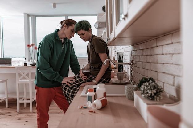 Unterstützung der ehefrau. ehemann mit grüner jacke, der seine gestresste frau beim alkoholtrinken unterstützt