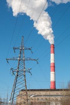 Unterstützung der hochspannungsleitung und rauch aus dem schornstein der industrieanlage.