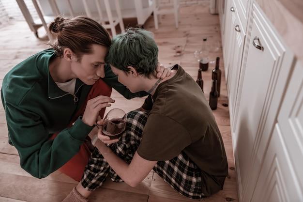 Unterstützung des ehemannes. draufsicht einer grünhaarigen frau, die depressiv ist und einen liebevollen ehemann unterstützt