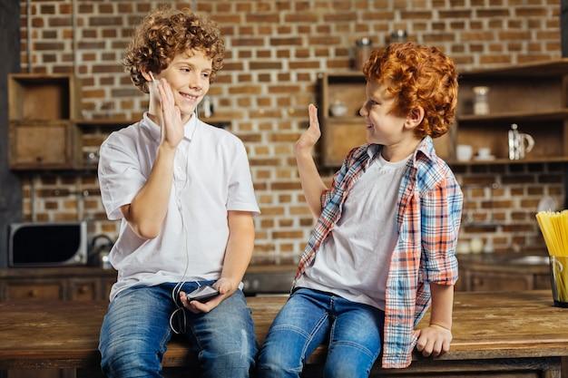Unterstützung ist das, worauf es wirklich ankommt. entspannte kinder lächeln, während sie sich ansehen und während eines angenehmen gesprächs zu hause eine high five geben.