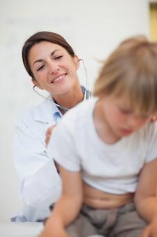Untersuchende atmung des doktors eines kindes mit einem stethoskop