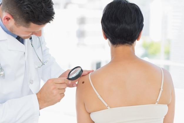 Untersuchender melanom des dermatologen auf frau