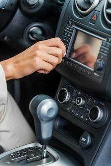 Untersucht ihr neues auto. nahaufnahme einer frau in formeller kleidung, die das armaturenbrett mit dem finger berührt, während sie im auto sitzt