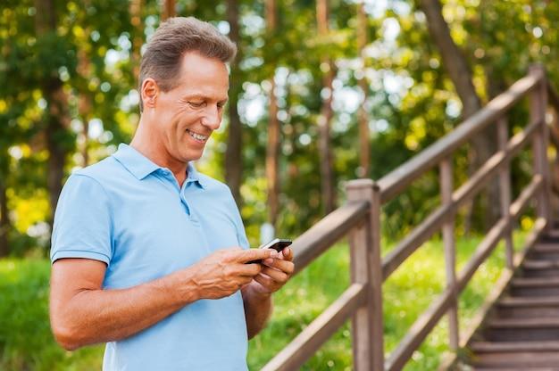 Untersucht sein brandneues smartphone. fröhlicher reifer mann, der handy hält und es mit einem lächeln betrachtet, während er an der holztreppe steht