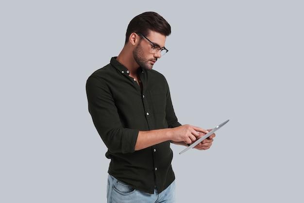 Untersucht sein digitales tablet. ernster junger mann mit brille, der an seinem digitalen tablet arbeitet, während er vor grauem hintergrund steht