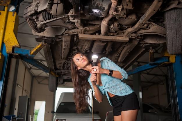 Untersuchung des sexy schönen mädchens angehobenes auto mit taschenlampe an der autoreparaturwerkstatt