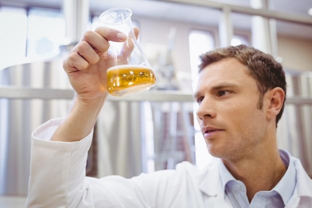 Untersuchungsbecher des fokussierten wissenschaftlers mit bier in der fabrik