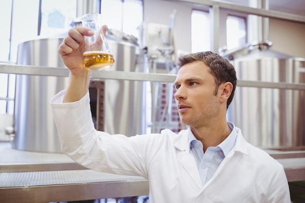 Untersuchungsbecher des fokussierten wissenschaftlers mit bier