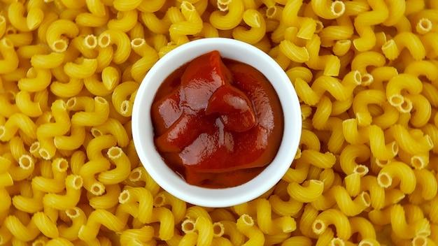 Untertasse mit köstlichem rotem ketchup auf hintergrund vieler trockener nudeln in form von spiralen.