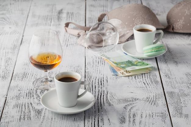 Unterwäsche, alkohol und geld als symbol für die kosten des sex.