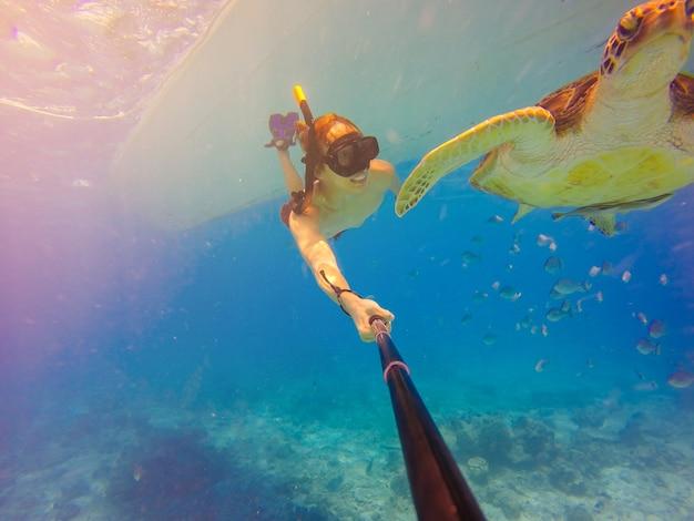 Unterwasser-selbstschuss mit selbststock. unterwasser-meerestierpostkarte. eine schildkröte sitzt bei korallen unter wasseroberfläche. tief blaues meer. weitwinkelaufnahme