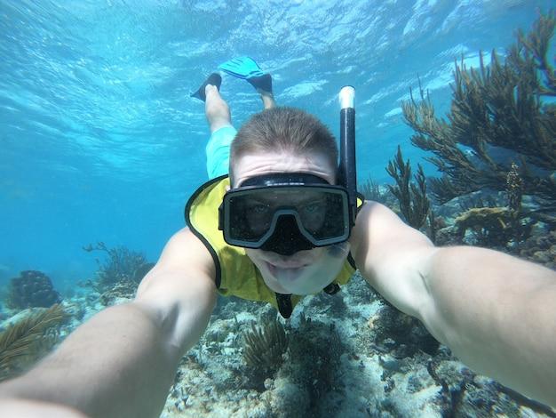 Unterwasser-weitwinkel-selfie des schwimmers in einem kristallklaren wasser mit marina-leben. mit lebensjaket