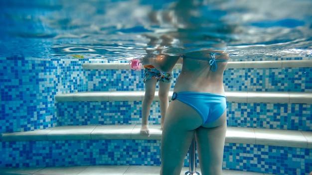 Unterwasserbild einer jungen mutter, die ihrem 3-jährigen kleinkind das schwimmen im pool beibringt