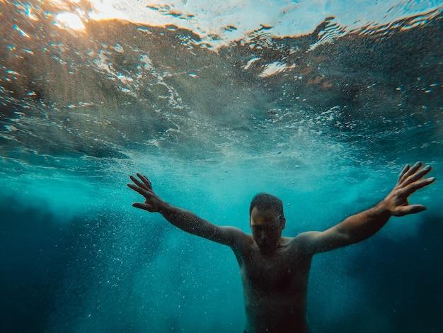 Unterwasserfoto des mannes auftauchend vom wasser