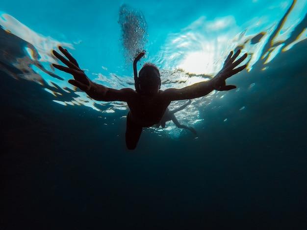 Unterwasserfoto des mannes schnorchelnd in einem meer
