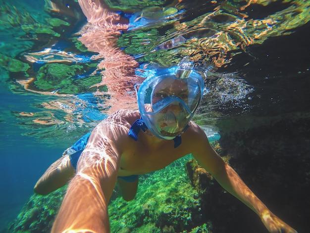 Unterwasserfoto eines jungen gesunden athletischen mannes mit einer schnorchelmaske, die im türkisfarbenen exotischen meer nahe den felsen taucht und ein selfie für sommerferien nimmt.