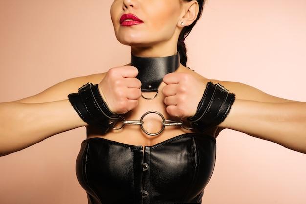 Unterwürfiges mädchen in schwarzem lederkorsett, handschellen und kragen wartet auf bestrafung. - bild