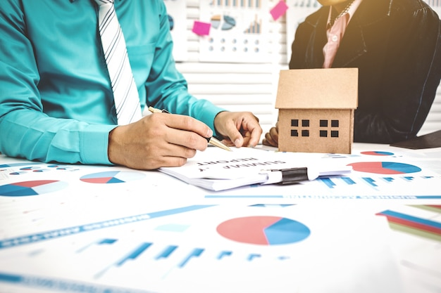 Unterzeichnen des papierarbeitshauskaufs mit vermittler und käufer.
