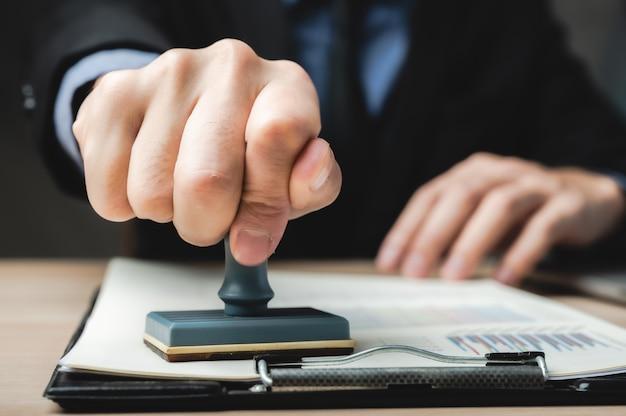 Unterzeichnen sie den genehmigten stempel auf dem dokument, um das arbeitsdokument und das visum am schreibtisch zuzulassen und zu zertifizieren