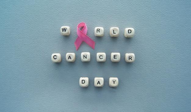 Unterzeichnen sie den weltkrebstagstext und das rosa band auf dem grauen hintergrund. prävention und medizinisches konzept
