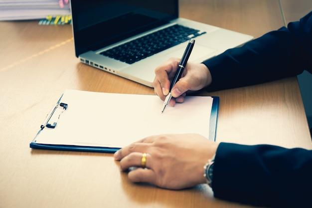 Unterzeichnende vertragsform des geschäfts erfolgreiche hand auf hölzernem schreibtisch im büro.
