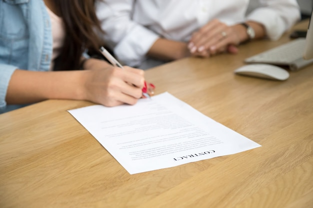 Unterzeichnender vertrag der frau, weibliche hand, die schriftliche unterzeichnung auf dokument setzt