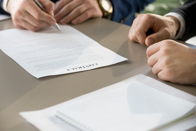 Unterzeichnender vertrag des geschäftsmannes bei der sitzung, fokus auf dokument, clos