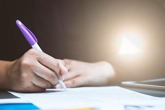 Unterzeichnender vertragsvertrag der nahaufnahmegeschäftsperson mit diagrammdatendokument auf schreibtisch