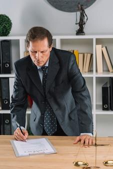 Unterzeichnendes vertragsdokument des reifen männlichen rechtsanwalts vor gerechtigkeitsskala