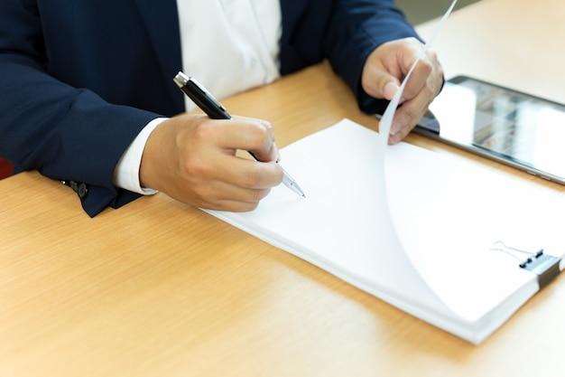 Unterzeichnendes vertragspapier des geschäftsmannes mit stift im schreibtisch.