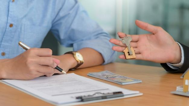 Unterzeichnung eines vertrags und lieferung der hausschlüssel für den kauf und verkauf von häusern.