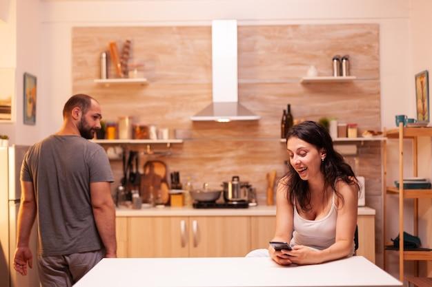Untreue frau, die zu hause in der nähe ihres mannes plaudert. eifersucht verzweifelter mann betrogen, wütend, frustriert und irritiert, findet nachrichten der untreue auf dem telefon der frau, die in der küche sitzt.