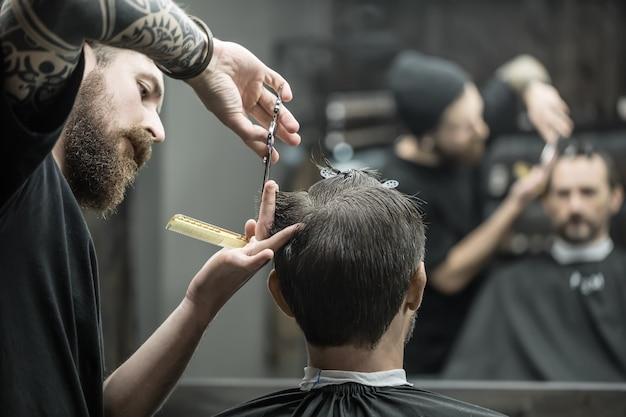 Unübertroffener friseur mit großem bart schneidet die haarspitzen seines kunden im schwarzen haarumhang im friseursalon