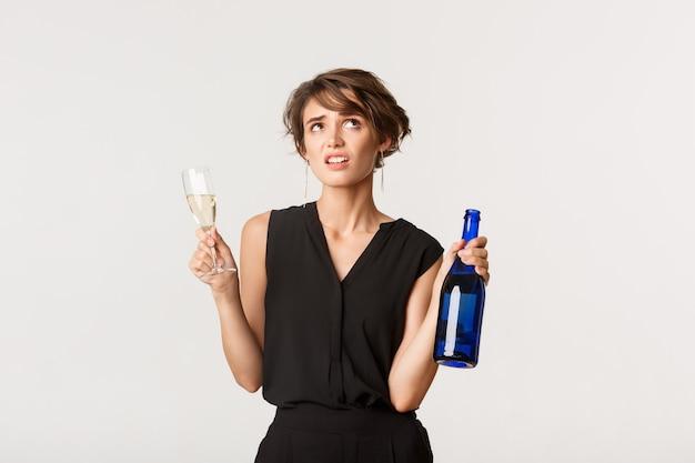 Unverblüfftes arrogantes mädchen rollte mit den augen, trank champagner auf langweiliger party und stand über weiß.