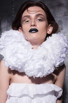 Unverschämt gekleidete frau mit extravagantem make-up und frisur posiert