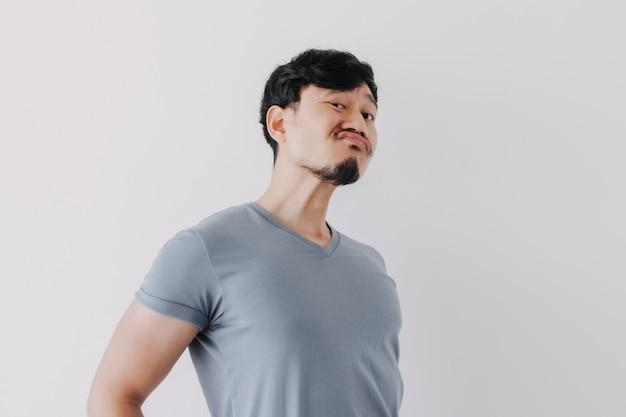 Unverschämt leugnendes gesicht des mannes im blauen t-shirt isoliert auf weißem hintergrund